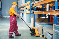 Worker with fork pallet truck. Stacker in warehouse loading furniture panels Royalty Free Stock Image