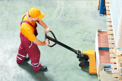 Worker with fork pallet truck stock images