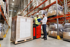 Worker on forklift and businessman at warehouse Royalty Free Stock Photography