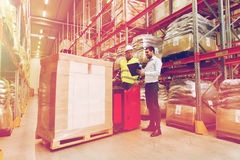 Worker on forklift and businessman at warehouse Royalty Free Stock Photo