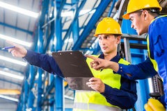 Worker and forklift driver in industrial factory royalty free stock photography