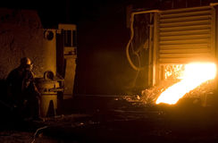 Worker in foundry. Worker takes a sample at steel company stock photos