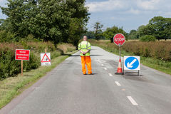 Worker in front of road closed signs on a UK road. Workman stands in front of a road closed sign near resurfacing work on an English country road Royalty Free Stock Images