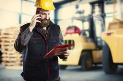 Worker in front of forklift Stock Images