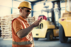 Worker in front of forklift Stock Photo