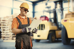 Worker in front of forklift Stock Photos