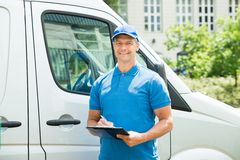 Worker In Front Of Truck Writing On Clipboard Royalty Free Stock Photography
