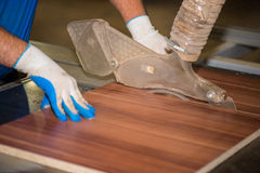 Worker on furniture factory. Worker with protection gloves  on furniture factory cutting furniture Stock Image