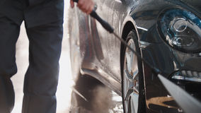 Worker in garage automobile service is washing a car in the suds by water hoses, detail close up Royalty Free Stock Photo