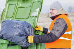 Worker with garbage bag near the container Royalty Free Stock Photos