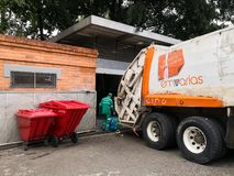 Worker garbage collector and a trash truck parked in industrial dumpster. Medellin, Antioquia, Colombia - 10/05/2018: Worker garbage collector with green uniform stock photo