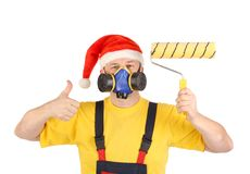 Worker in gas mask and santa hat with roller Royalty Free Stock Images
