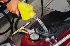 Worker At Gas Station Filling Up Customers motorcycle With gasoline. stock photos