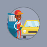 Worker of gas station filling up fuel into car. African-american gas station worker filling up fuel into the car. Gas station worker in workwear. Gas station Royalty Free Stock Photos