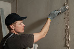 Worker gets plaster on the wall Royalty Free Stock Photos