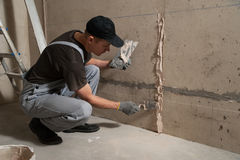 Worker gets plaster on the wall Royalty Free Stock Photography