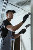 Worker gets plaster on the wall Stock Image