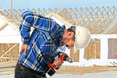 Worker Getting back injury. Hispanic worker getting back injury on construction site Royalty Free Stock Images