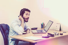 Worker getting some shocking news over the phone. Man looks very surprised during phone call. Minimalistic workstation with laptop and some office supplies stock images