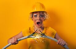 Free Worker Girl With Hat Breaks An Electric Cable. Yellow Background Royalty Free Stock Photo - 185945585