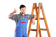 Worker giving thumb. A manual worker standing next to a wooden ladder and giving thumb up isolated on white Stock Photography