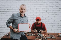 Old Man Holding White Plastic Tablet in Workshop. royalty free stock image
