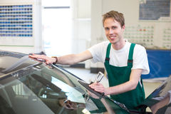 Worker in glazier's workshop installs windshield Royalty Free Stock Photo