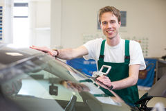 Worker in glazier's workshop installs windshield Royalty Free Stock Photography