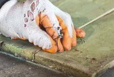 Clogging a nail in a wooden board. Worker in gloves holding and clogging a nail in a wooden board Royalty Free Stock Photos