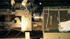 Worker with gloves to adjust the lathe when manufacturing parts. Master moves with the lever of the mechanism for the precise execution of the work assignment stock footage