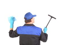 Worker in gloves with window cleaner. Royalty Free Stock Image