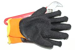 Worker gloves and wrench on white place stock photography