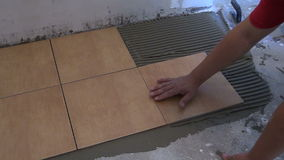 Worker glue ceramic tile on floor at home. Home renovation stock video