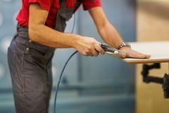 Worker with glue gun and board at workshop Stock Images