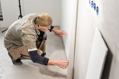 Worker glueing wallpapers on concrete wall. Repair the apartment. Home renovation concept. White Wallpaper for paint. Young man, worker glueing wallpapers on royalty free stock image
