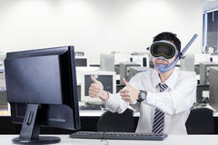 Worker with goggles and snorkel at workplace. Male worker wearing goggles and snorkel in the office and showing thumbs up on the monitor Royalty Free Stock Images