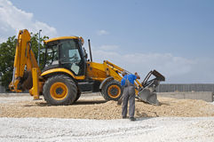 Worker and gravel excavator Stock Photography