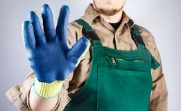Worker in green overall outfit showing blue glove. Photo of a worker in green overall outfit showing protective rubber blue glove on grey background torso view royalty free stock photo