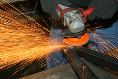 Worker with grinder. Welder grinding metal frame; making sparks Royalty Free Stock Image