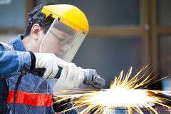 Worker with grinder machine cutting metal. In factory Stock Image