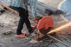 Worker with grinder machine cutting metal reinforcement rebar rods. Construction builder worker with grinder machine cutting metal reinforcement rebar rods at royalty free stock images