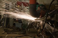 Worker grinding. Steel, sparks flying Royalty Free Stock Photos