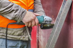 Worker with grinding machine cutting iron Royalty Free Stock Photography