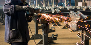 Worker grinding metal with angle grinder. Worker grinding metal with a angle grinder Royalty Free Stock Image