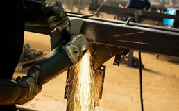Worker grinding metal with angle grinder. Worker grinding metal with an angle grinder Stock Photos