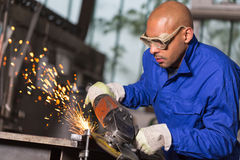 Worker grinding metal with angle gringer Royalty Free Stock Image
