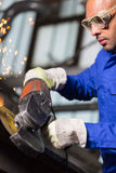 Worker grinding metal with angle gringer Stock Photos