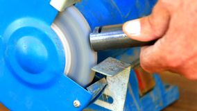 Worker grinding metal component on bench grinder stock footage