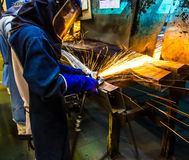 Worker grinding metal. The worker grinding metal in manufacturing plant Royalty Free Stock Photography