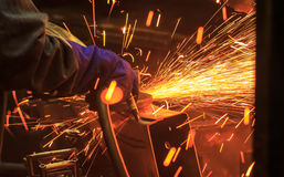 The worker grinding metal. In manufacturing plant Stock Image